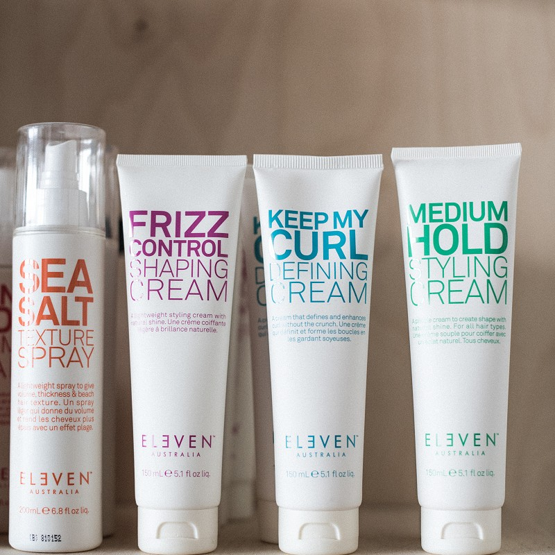 Various Eleven Australia haircare products arranged on a shelf